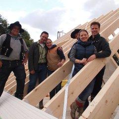 Bauherren mit Nachbarn und Zimmermännern